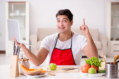 The man with laptop preparing food at the kitchen Royalty Free Stock Photography