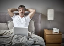 Man with laptop relaxing in bed. Royalty Free Stock Images