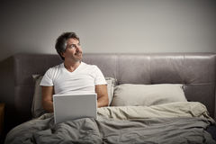 Man with laptop relaxing in bed. Stock Image