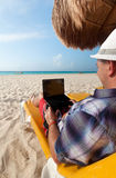 Man with laptop relaxing on the Caribbean beach Stock Photo