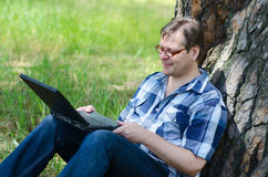Man with laptop is resting in forest near old pine. Man with laptop is resting in forest near large trunk of old pine tree Stock Photos