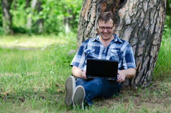 Man with laptop is resting in forest near old pine. Man with laptop is resting in pine forest near large trunk of old pine tree in sunny summer day Stock Images