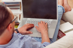 Man on laptop running business from home. Closeup portrait of businessman working on laptop computer from home while lying on sofa or couch. Business or stock photo
