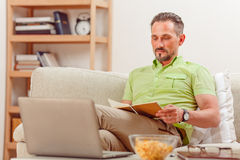 Man on laptop running business from home. Home business concept. Handsome businessman reading something while laptop computer represented in front of him at home stock image