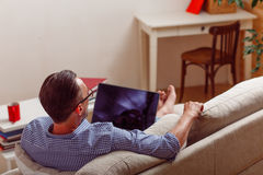 Man on laptop running business from home. Handsome man running business from home. Back view of handsome man speaking over smart phone while lying on sofa or Stock Images