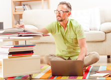 Man on laptop running business from home. Handsome man in glasses working from home. Businessman in glasses using laptop computer and trying to prepare new stock photography