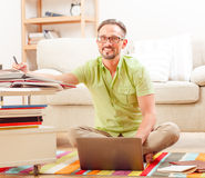 Man on laptop running business from home. Portrait of handsome businessman in glasses sitting on floor and working on his laptop compuer from home. Business and stock images