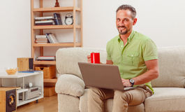 Man on laptop running business from home. Portrait of handsome man sitting on sofa and drinking cup of tea or coffee. Happy man working on laptop computer from royalty free stock photography