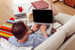 Man on laptop running business from home. Top view of handsome man lying on sofa or couch and using laptop computer from home. Business or freelance concept royalty free stock image