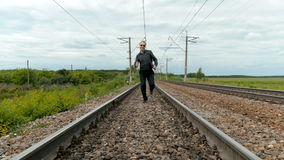 A man with a laptop runs along the railroad tracks. stock video footage