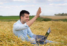 Man with laptop saluting. Young attractive man with laptop sitting on haystack at farmland and waving hand to someone Stock Images
