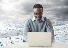 Man on laptop in sea of documents under sky clouds. Digital composite of man on laptop in sea of documents under sky clouds Stock Photography