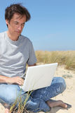 Man on laptop at the seaside Stock Photos