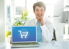 Man with laptop with Shopping trolley icon stock photography