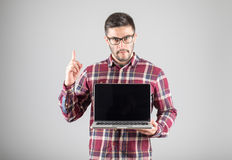Man with laptop showing attention gesture. Attractive man with laptop showing his forefinger. Good idea or attention gesture Stock Photo