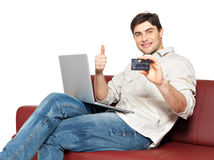 Man with laptop shows the credit card Stock Image
