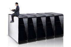 Man with laptop sits on computer servers Stock Images