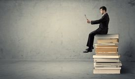Man with laptop sitting on books. A serious businessman with tablet in hand in suit sitting on a pile of giant books in front of a textured grey wall Royalty Free Stock Image