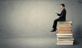 Man with laptop sitting on books. A serious businessman with tablet in hand in suit sitting on a pile of giant books in front of a textured grey wall Stock Image