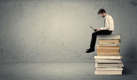 Man with laptop sitting on books. A serious businessman with tablet in hand in suit sitting on a pile of giant books in front of a textured grey wall Stock Photography