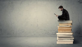 Man with laptop sitting on books Royalty Free Stock Image