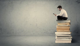 Man with laptop sitting on books. A serious businessman with tablet in hand in suit sitting on a pile of giant books in front of a textured grey wall Stock Photo