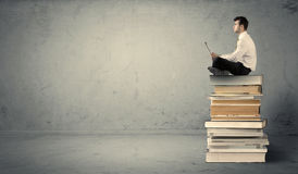 Man with laptop sitting on books. A serious businessman with tablet in hand in suit sitting on a pile of giant books in front of a textured grey wall Royalty Free Stock Images