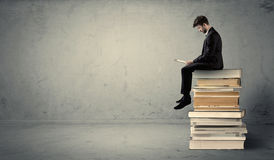 Man with laptop sitting on books. A serious businessman with tablet in hand in suit sitting on a pile of giant books in front of a textured grey wall Royalty Free Stock Photos