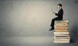 Man with laptop sitting on books Stock Photo
