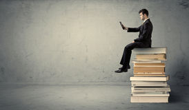 Man with laptop sitting on books. A serious businessman with tablet in hand in suit sitting on a pile of giant books in front of a textured grey wall Royalty Free Stock Photography