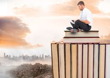 Man with laptop sitting on Books stacked by distant city and clouds Stock Image