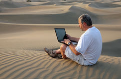 Man with laptop sitting in desert. Royalty Free Stock Images