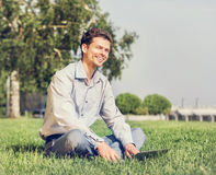Man with laptop sitting on green lawn Royalty Free Stock Photos