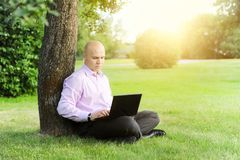 Man with laptop sitting near a tree Royalty Free Stock Photos