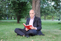 Man with laptop sitting near a tree. In the park Stock Images
