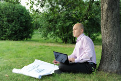 Man with laptop sitting near a tree Stock Photo