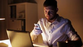 Man with laptop and smartphone at night office stock video footage
