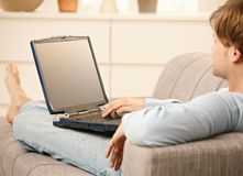 Man with laptop on sofa Royalty Free Stock Image