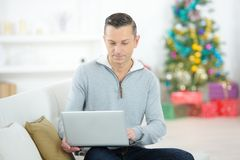 Man with laptop on sofa at christmas time royalty free stock image