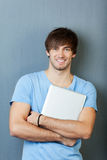 Man With Laptop Standing Against Blue Wall. Portrait of confident young man laptop standing against blue wall Royalty Free Stock Images