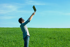 Man with laptop standing in a field Stock Photography