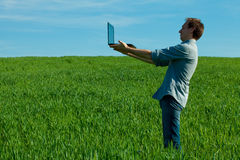 Man with laptop standing in a field Royalty Free Stock Photos