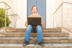 Man with laptop on steps Royalty Free Stock Photography