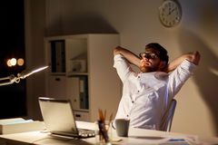 Man with laptop stretching at night office. Business, overwork, deadline and people concept - tired man with laptop working at night office and stretching Stock Image