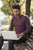Man with laptop at summer park on bright day.  royalty free stock photography
