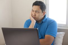 Man with Laptop, Thinking Expression stock photo