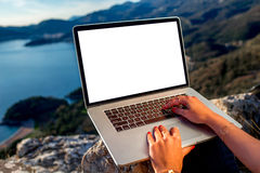 Man with laptop on the top of mountain. Woman working with laptop on the top of mountain with beautiful landscape on background. Blogging concept Stock Images