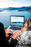 Man with laptop on the top of mountain Stock Photos