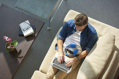 Man with laptop. Top view shot of a casual man using laptop while sitting at her home royalty free stock photo