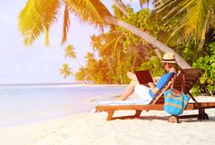 Man with laptop on tropical beach. Vacation Stock Image